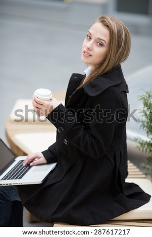Young woman sitting on the bench with cup of coffee and laptop. - stock photo