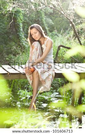 young woman sitting on the bridge - stock photo