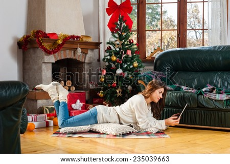 Young woman sitting on the floor, alone, in front of christmas tree on living room,using tablet pc. - stock photo