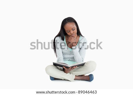 Young woman sitting on the floor reading in her book against a white background - stock photo