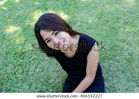 young woman sitting on the grass and enjoying in the sunny day. Portrait of asian. - stock photo