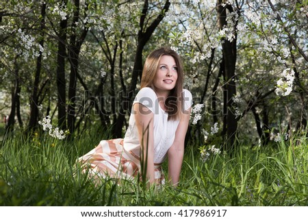 Young woman sitting on the grass in the lush garden. Spring portrait in nature - stock photo