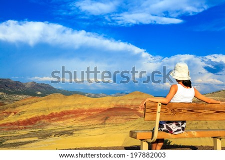 Young woman sitting on the hill-top bench relaxing while watching the colorful Painted hills at John Day Fossil Beds National Monument, Oregon - stock photo
