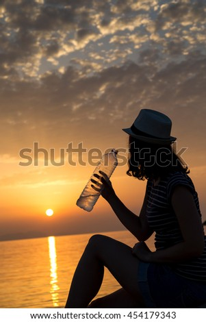 Young woman sitting on the rocky shore, drinking water and enjoying a beautiful sunset in Syvota bay, Greece - stock photo
