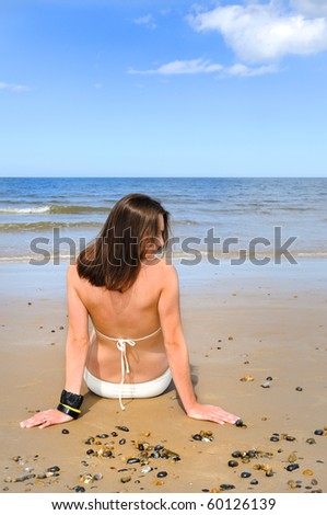 young woman sitting on the sand. - stock photo