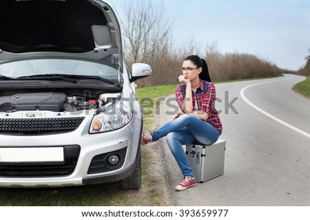 Young woman sitting on the suitcase beside stopped car with opened hood by the road - stock photo