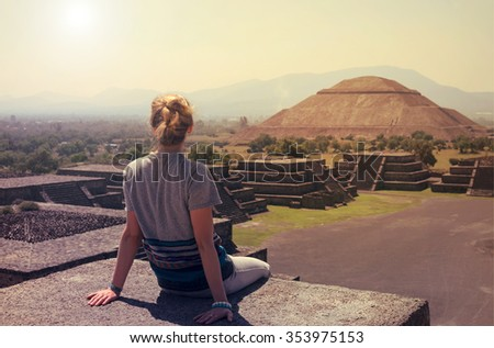Young woman sitting on the top of pyramid overlooking Teotihuacan at the sunset  - stock photo
