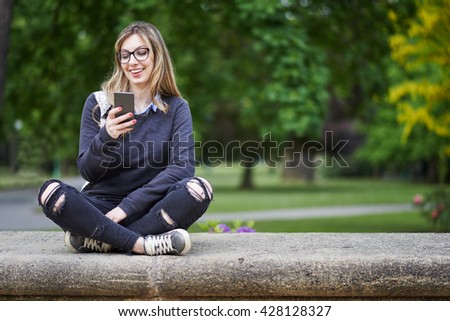 Young woman sitting on the wall in the park, writing a message on her mobile phone, park in the background - stock photo