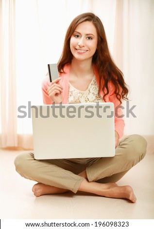 Young woman sitting on thr floor with laptop and holding credit card - stock photo