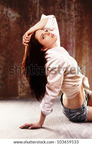 young woman sitting on wooden floor in front of a rusty background - stock photo