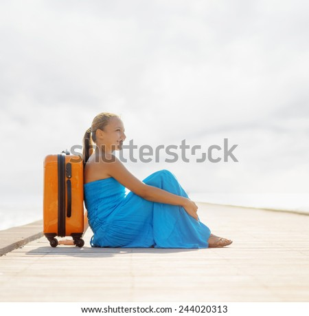 Young woman sitting on wooden pier. - stock photo