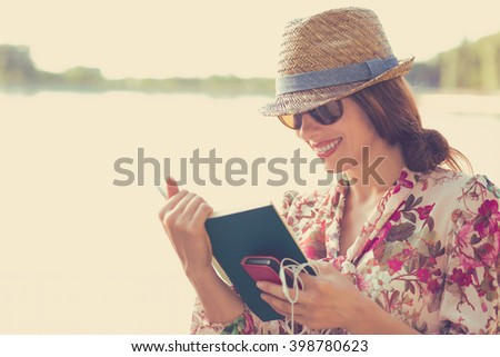 young woman sitting outdoors and reading a book - stock photo
