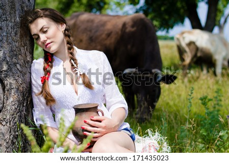 Young woman sitting tired near cows in countryside - stock photo