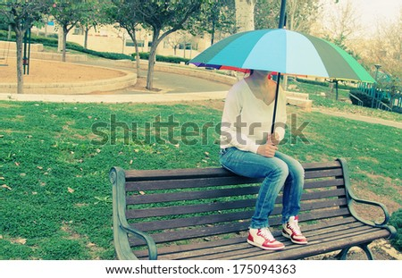 Young woman sitting under a big rainbow umbrella - stock photo