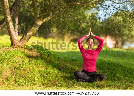 young woman sitting under a tree and meditating, selective focus - stock photo