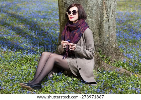 Young woman sitting under the tree, on the grass holding a flower in her hands. - stock photo