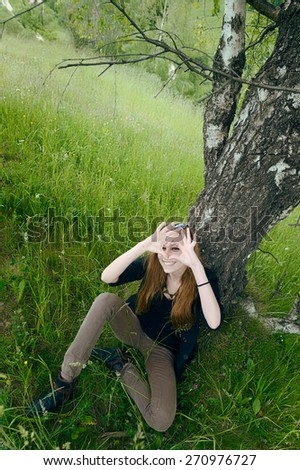 Young  woman sitting under tree  shaping heart with fingers in front of eyes  - stock photo