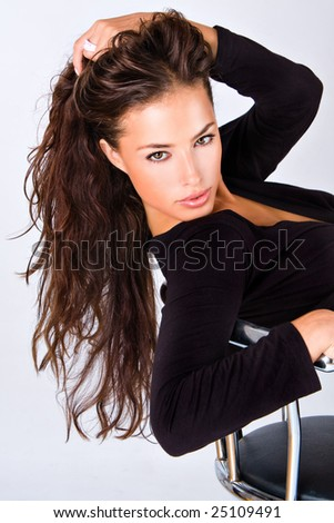 young woman sitting with hand in hair - stock photo