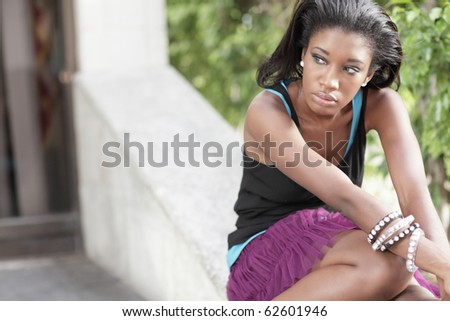 Young woman sitting with hands on her knees - stock photo