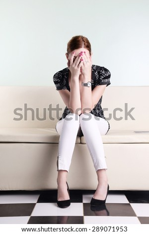 Young woman sitting with hands over her face, bored, worried or stressed - stock photo