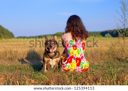 Young woman sitting with her dog on the meadow at sunset. Dog looking at the camera, woman sitting back to camera. - stock photo