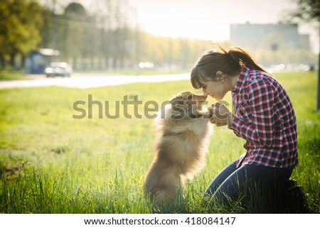 Young woman sitting with her dog sheltie on the grass and playing with the shetland sheepdog - stock photo