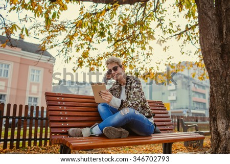 Young woman sitting with Tablet and reading - stock photo