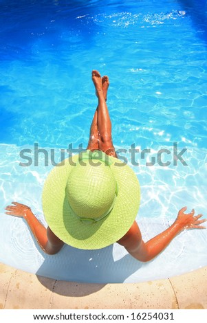 Young woman sittingin a swimming pool with a green hat - stock photo