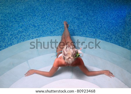 Young woman sittingin in a swimming pool - stock photo