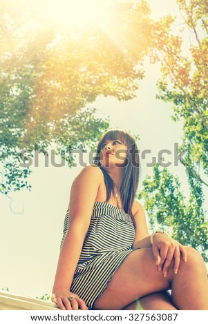 Young woman sittting backlit in summer dress, low angle view. - stock photo