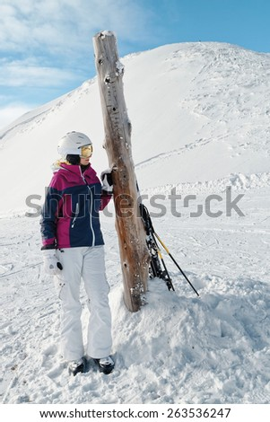Young woman skier against a white winter mountains background - stock photo