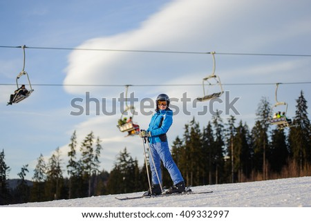 Young woman skier against ski-lift and forest on a sunny day. Girl is wearing helmet skiing glasses, gloves and blue ski suit. Ski resort at Carpathian Mountains, Bukovel, Ukraine - stock photo