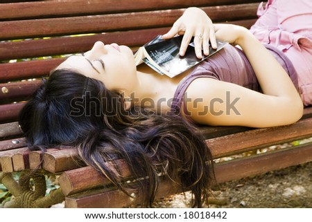 Young woman sleeping in a bench after reading a bool. - stock photo