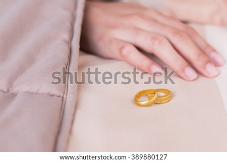 Young woman sleeping in bed with wedding-rings. - stock photo