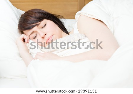 Young woman sleeping in her wooden bed - stock photo