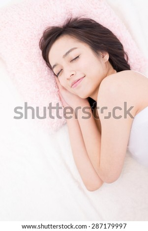 young woman sleeping on a bed - stock photo