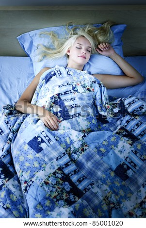 Young woman sleeping peacefully at night in bed - stock photo