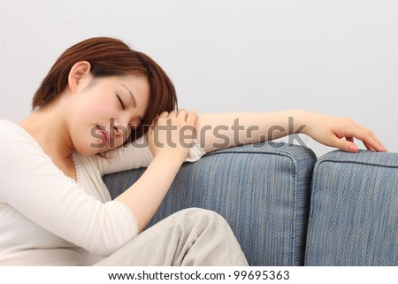 young woman sleeps on a bed in a bedroom at home - stock photo