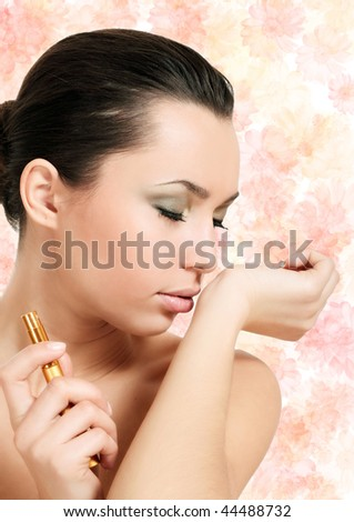 young woman smelling parfume on floral background - stock photo