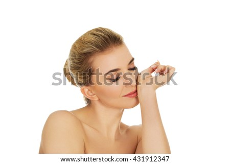 Young woman smelling perfume on her wrist. - stock photo