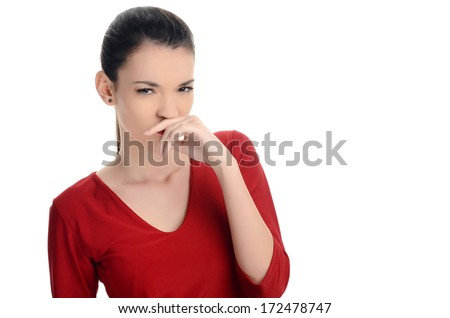 Young woman smelling something bad. Dissgusting odor. Girl squinting and holding her hand at her nose. Isolated on white background. - stock photo