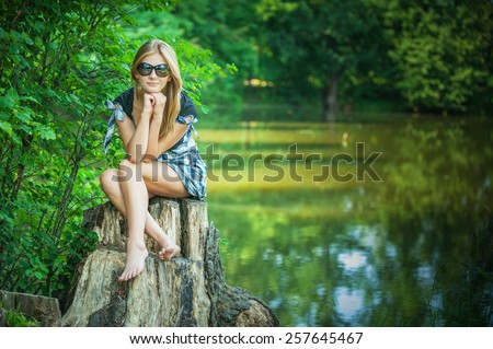 Young woman smiles in black glasses on stub, in summer city park. - stock photo