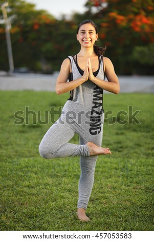 Young woman smiling and performing a yoga pose - stock photo