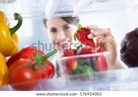 Young woman smiling and taking a fresh strawberry from refrigerator. - stock photo