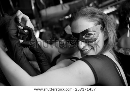 young woman smiling and wearing mask - stock photo