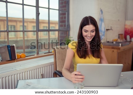Young woman smiling as she surfs the internet on her laptop computer while sitting at a table in front of a window in her urban apartment - stock photo