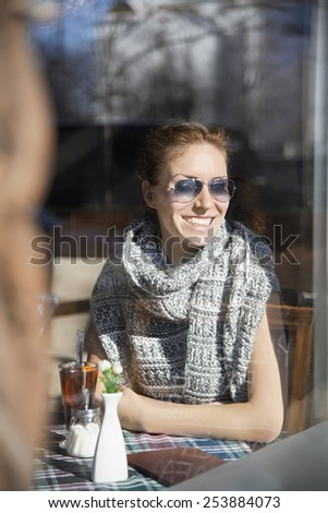 Young woman smiling behind the window of restaurant/A beautiful confident smiling young woman with stylish sunglasses, sitting and drinking red hot wine in restaurant. Shoot trough the window - stock photo