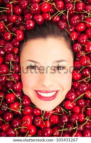 Young woman smiling face portrait surrounded by cherries. - stock photo