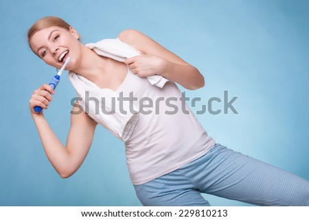 Young woman smiling girl with toothbrush brushing her white teeth on blue. Daily dental care. Studio shot. - stock photo