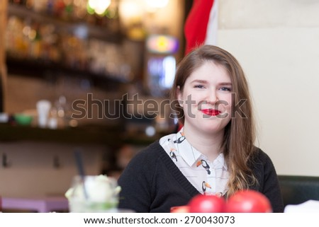 young woman smiling in coffee shop  - stock photo